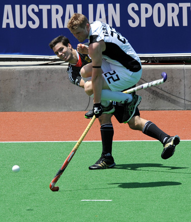 Blair Tarrant (R) of New Zealand leaps as Patrick Schmidt of Germany passes the ball during their men's hockey match at the Champions Trophy on December 1, 2012. ? Photo by AFP