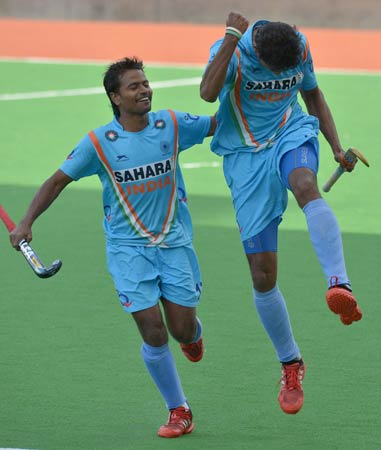 Birendra Lakra of India (Left) congratulates teammate Nithin Thimmaiah after scoring a goal against Germany in their Pool A Pool A match at the Men's Hockey Champions Trophy tournament in Melbourne on December 4, 2012. Germany won the match 3-2.