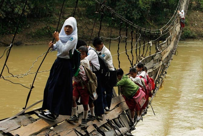 Students hold on to the side steel bars of a collapsed bridge as they cross a river to get to school at Sanghiang Tanjung village in Lebak regency, Indonesia's Banten village January 19, 2012. Flooding from the Ciberang river broke a pillar supporting the suspension bridge, which was built in 2001, according to Epi Sopian the head of Sanghiang Tanjung village.