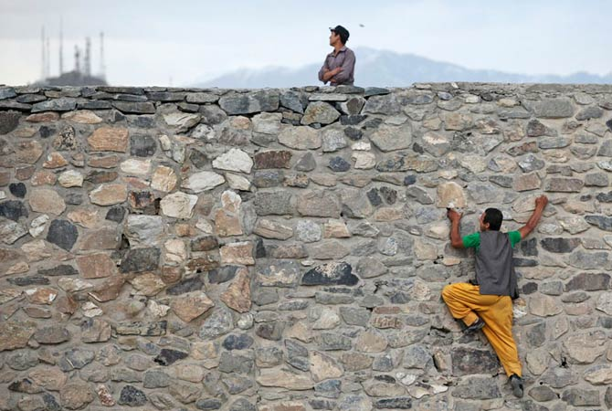 An Afghan man takes a shortcut by climbing a wall, at a hilltop in Kabul May 11, 2012.
