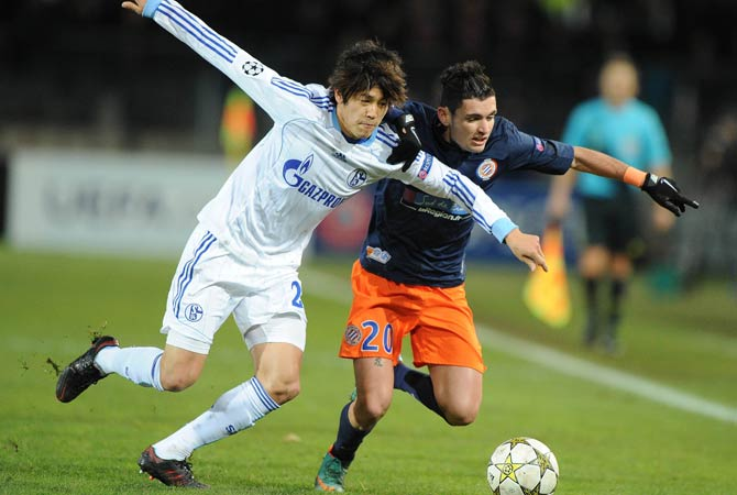 Montpellier's French midfielder Remy Cabella (Right) vies with Schalke's Japanese defender Atsuto Uchida  (Left) during the UEFA Champions League football match Montpellier vs. Schalke.