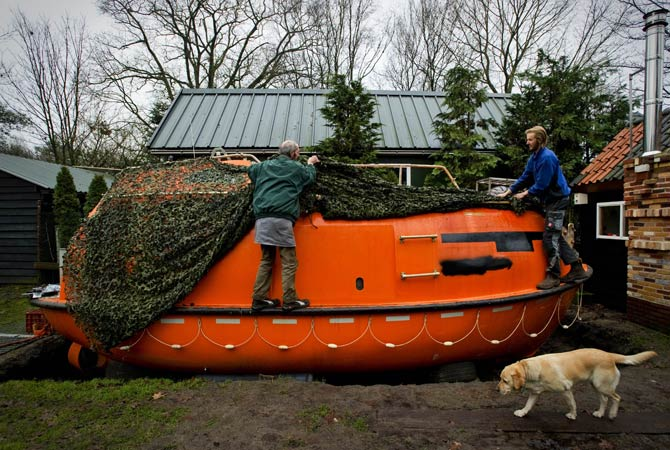 Duch Pieter van der Meer (Left) and a friend uncover on December 19, 2012 his Norwegian lifeboat in his garden in Kootwijkerbroek with which he can save 35 persons in case of a global apocalypse hits on 21 December.. ? Photo by AFP