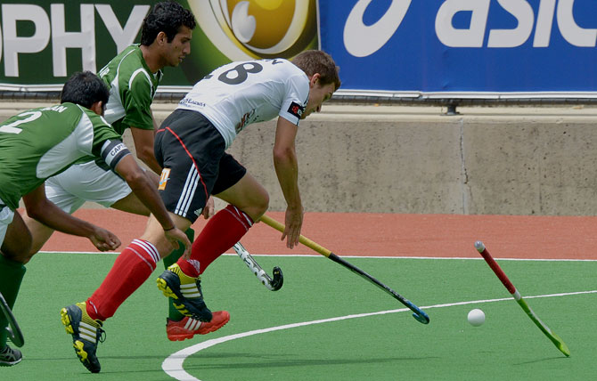 Oliver Korn of Germany (R) fights for the ball with Captain Muhammad Imran (L) and Muhammad Rizwan Jnr of Pakistan (C) and during the first quarter final at the Men's Hockey Champions Trophy in Melbourne on December 6, 2012. Pakistan beat the number one ranked Germany 2-1. ? Photo by AFP
