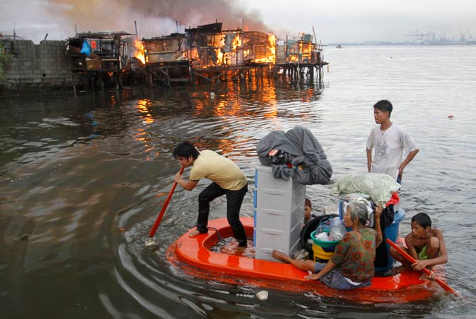 Residents paddle their makeshift boat to safety as fire engulfs houses at a slum community in Manila May 11, 2012. At least 1000 houses were razed in the fire, leaving 5000 families homeless, local media reported.