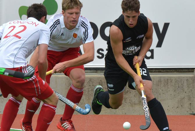 Nicholas Wilson of New Zealand (Right) powers past defenders Oliver Willars and David Condon (Left) of England during their Pool A match at the Men's Hockey Champions Trophy tournament in Melbourne on December 4, 2012.