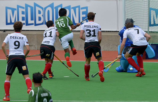 Felix Reuss of Germany deflects a ball from as Ali Shan of Pakisan (C) leaps during the first quarter final at the Men's Hockey Champions Trophy in Melbourne on December 6, 2012. Pakistan beat the number one ranked Germany 2-1. ? Photo by AFP