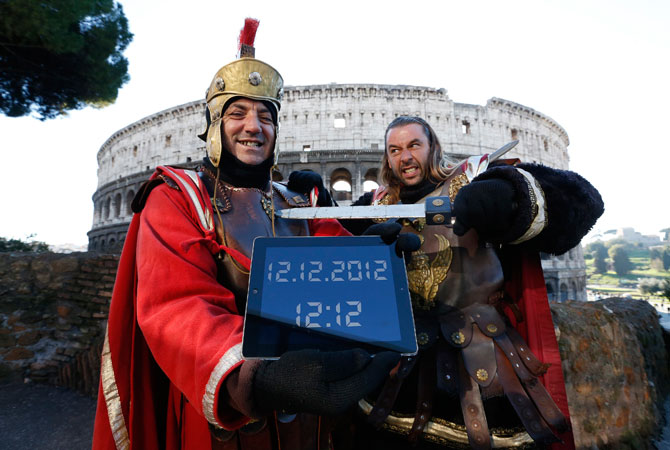 People dressed as Centurions pose with an iPad showing the date ?12.12.2012? in front of Rome's ancient Colosseum December 12, 2012. The day was seen as auspicious as it is rare that a date contains three ?12's.