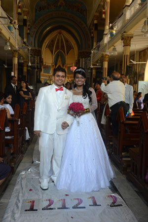 Groom Brandon Pereira (L) and his bride Emilia D'Silva pose after their marriage at the Mount Mary church in Mumbai on December 12, 2012. Couples may be rushing down the aisle on 12/12/12 today in hope of an auspicious union, but Brandon Pereira and Emilia D'Silva can claim an even rarer set of special dates. Brandon Pereira and Emilia D'Silva who have known each other for over 10 years now celebrated their engagement on 10/10/10, had a registered legal marriage on 11/11/11 and finally had their big white wedding i