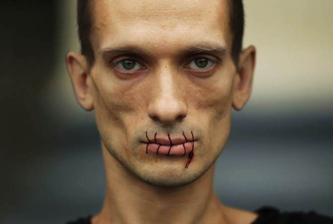 "Artist Pyotr Pavlensky, a supporter of jailed members of female punk band ""Pussy Riot"", looks on with his mouth sewed up as he protests outside the Kazan Cathedral in St. Petersburg, July 23, 2012."