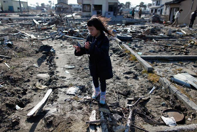 Wakana Kumagai, 7, visits the spot where her house, which was washed away by the March 11, 2011 tsunami, used to stand in Higashimatsushima, Miyagi prefecture March 11, 2012, to mark the first anniversary of an earthquake and tsunami that killed thousands and set off a nuclear crisis.