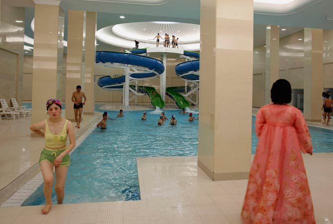 A woman in traditional Korean costume watches as a student leaves a swimming pool of Kim Il-sung University in Pyongyang April 11, 2012.