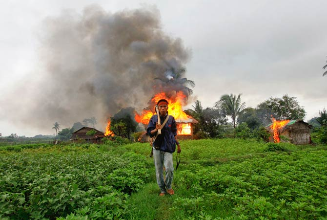 An ethnic Rakhine man holds homemade weapons as he walks in front of houses that were burnt during fighting between Buddhist Rakhine and Muslim Rohingya communities in Sittwe June 10, 2012.