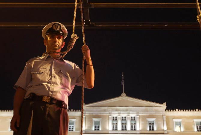 A police officer pretends to hang himself in front of the parliament during a rally in Athens September 6, 2012. About 4,000 Greek police, coastguards and firemen protested in Athens on Thursday, staging faked suicides on gallows they placed outside the finance ministry and parliament to symbolise the pain of budget cuts.