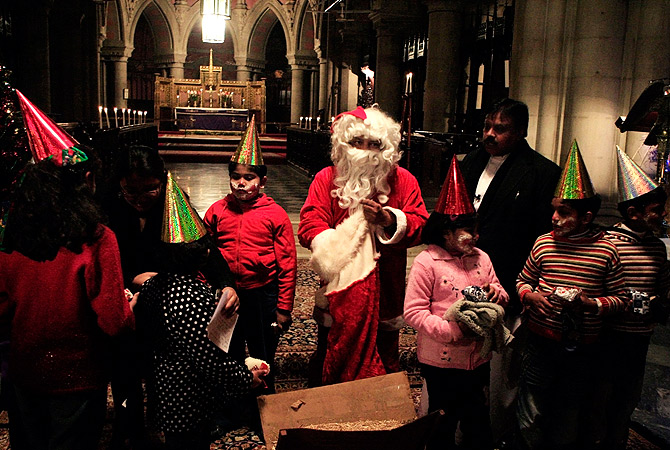 A Pakistani man dressed as Santa Claus distributes gifts to children at a local church in Lahore, Pakistan. ? AP Photo
