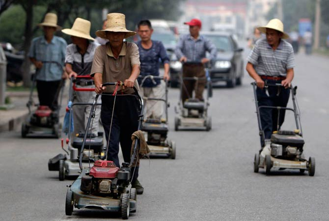 Residents push lawn mowers on a street in Nanjie village of Luohe city in China's central Henan province September 24, 2012. Nanjie village, with more than 3,100 residents, is touted to be one of the remaining models of communist China, where the principles of morality and collectivism of the late Chairman Mao still strictly guide the people's daily lives. Aside from free housing, healthcare, food rations and education, locals working in the village's factories receive an average salary of 2500 yuan, about 400 dol