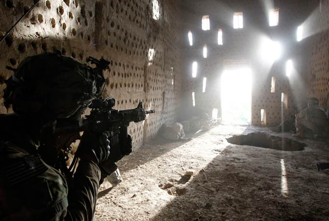U.S. soldier Nicholas Dickhut from 5-20 infantry Regiment attached to 82nd Airborne points his rifle at a doorway after coming under fire by the Taliban while on patrol in Zharay district in Kandahar province, southern Afghanistan April 26, 2012.