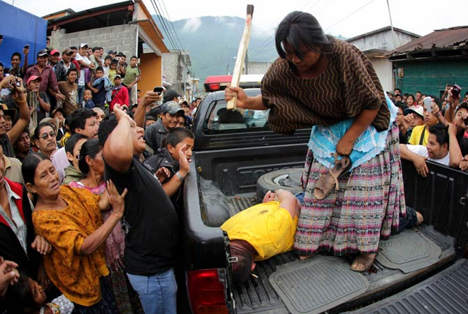A woman hits a man with a stick after he is accused of theft along with three other men at Tactic, in the Alta Verapaz region, about 189 km (117 miles) from Guatemala City, September 13, 2012. The local community tied up and beat four men who were accused of theft in the aftermath of a school killing. The man, who had entered a classroom and killed two children, ages 8 and 13, with a machete, was lynched and burnt alive by a mob, local media reported.