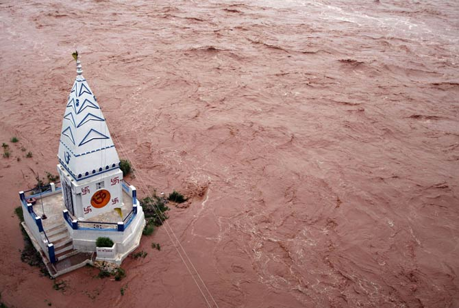 A temple stands amid the waters of the flooded river Tawi after heavy rains in Jammu August 19, 2012.