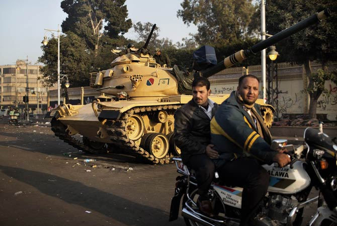 Two Egyptian men ride a motorbike past a tank stationed outside the presidential palace in Cairo.