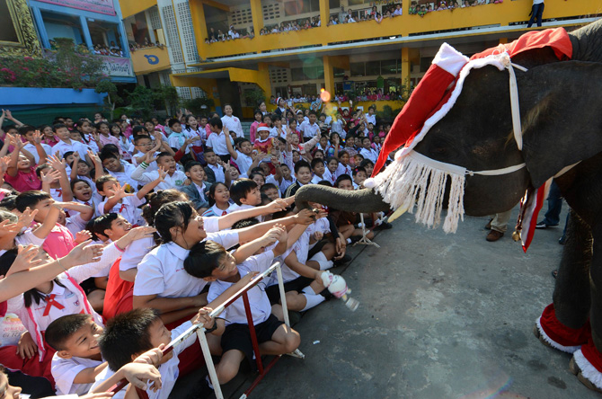 An elephant dressed in a Santa Claus costume gives gifts to students ahead of the Christmas festival at a school in Ayutthaya province on December 24, 2012.  The event was held as part of a campaign to promote Christmas in Thailand. ? Photo by
