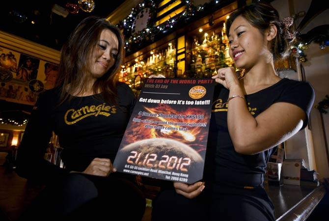 Yashen (Right) and Neetu, staff of the bar Carnegie's, pose as they hold a flyer for the ?end of the world' party, in Hong kong on December 21, 2012. ? Photo by AFP