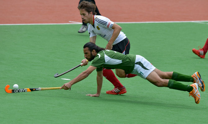 Shakeel Abbasi of Pakistan (front) dives for the ball ahead of Benedikt Fuerk of Germany during the first quarter final at the Men's Hockey Champions Trophy in Melbourne on December 6, 2012. Germany leads the match 1-0 at half-time. ? Photo by AFP