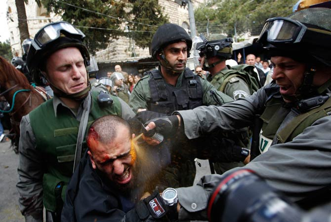 Israeli border police officers use pepper spray as they detain an injured Palestinian protester during clashes on Land Day after Friday prayers outside Damascus Gate in Jerusalem's Old City March 30, 2012. Israeli security forces fired rubber bullets, tear gas and stun grenades to break up groups of Palestinian stone-throwers as annual Land Day rallies turned violent.