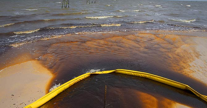 File photograph of a protective boom as oil from the Deepwater Horizon spill recedes back into the Gulf of Mexico after washing into a drainage canal in Waveland. - File Photo