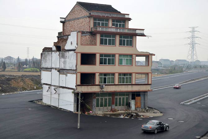 A car stops beside a house in the middle of a newly built road in Wenling, Zhejiang province, November 22, 2012. An elderly couple refused to sign an agreement to allow their house to be demolished. They say that compensation offered is not enough to cover rebuilding costs, according to local media. Their house is the only building left standing on a road which is paved through their village.