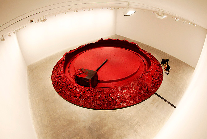Volunteers work next to 'My Red Homeland' by Indian-born British artist Anish Kapoor at the Museum of Contemporary Art in central Sydney December 18, 2012. The Anish Kapoor exhibition is part of the Sydney international art series and will run until April 1, 2013. ? Reuters Photo