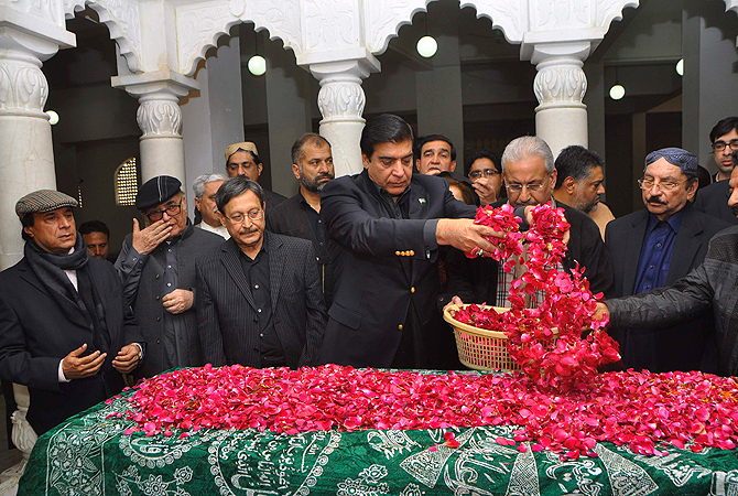 Pakistan's Prime Minister Raja Pervez Ashraf (C) scatters rose petals on the grave of Pakistan's former Prime Minister Benazir Bhutto during her death anniversary at the Bhutto family mausoleum in Garhi Khuda Bakhsh, near Larkana December December 27, 2012. ? Reuters Photo