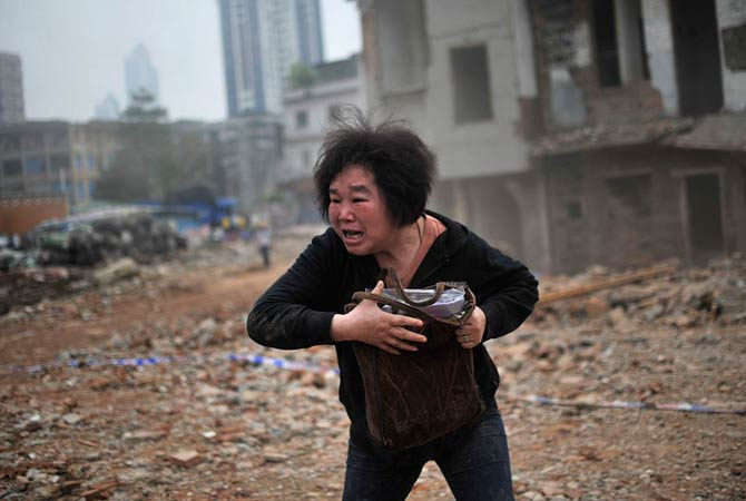 Huang Sufang reacts as she sees a part of her house being taken down by demolition workers at Yangji village in central Guangzhou city, Guangdong province March 21, 2012.