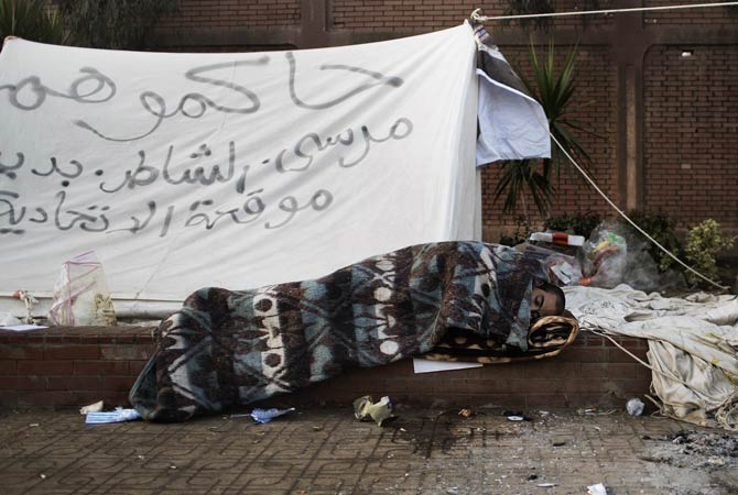 An Egyptian protestor sleeps on the pavement outside the presidential palace in Cairo on December.