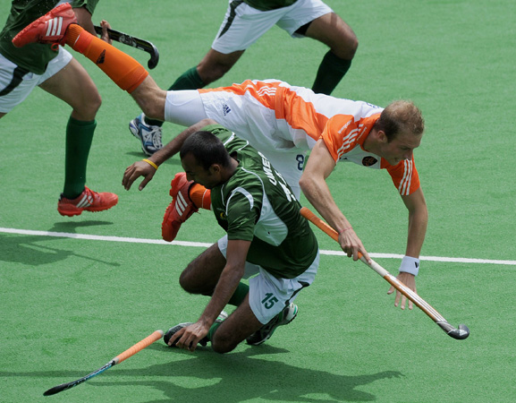 Billy Bakker of The Netherlands tumbles over Muhammad Umar Bhutta of Pakistan during their men's hockey match at the Champions Trophy in Melbourne on December 1, 2012. A? Photo by AFP