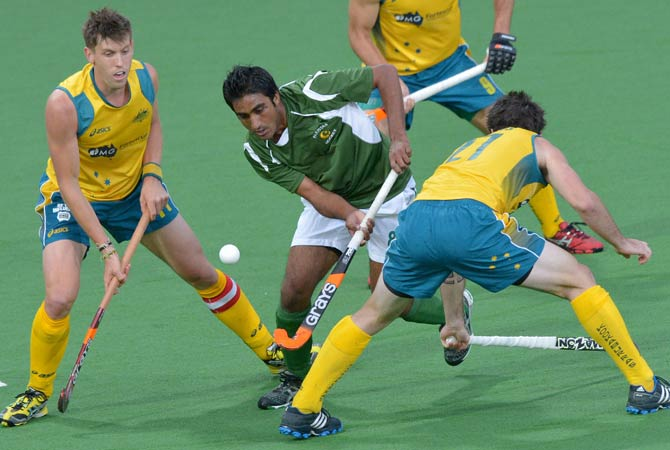 Shafqat Rasool of Pakistan fights his way though Kieren Govers (Right) and Eddie Ockenden of Australia (Left) during their Pool B match at the Men's Hockey Champions Trophy tournament in Melbourne on December 4, 2012. Australia won the match 1-0 at full-time.