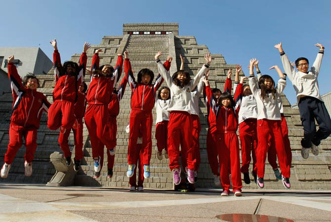 Students jump together to pose for photographers in front of a mock pyramid after the countdown time when many believe the Mayan people predicted the end of the world, Friday, Dec. 21, 2012, in Taichung, southern Taiwan. ? Photo by AP