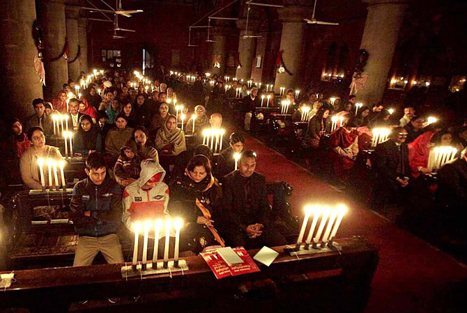 Christian busy in religious rituals during Christmas  eve at a church in Lahore. ? Photo by APP