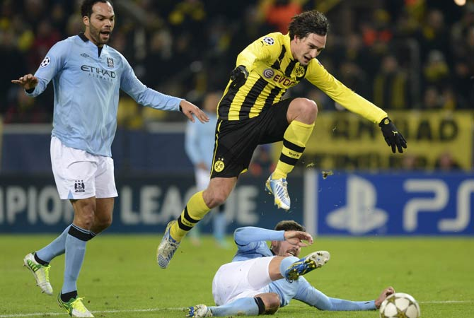Manchester's defender Joleon Lescott (Left), Manchester's Spain midfielder Javi Garcia (Centre) and Dortmund's defender Mats Hummels (Right) vie for the ball during the UEFA Champions League Group D football match Borrusia Dortmund vs Manchester City in Dortmund, western Germany
