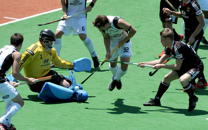 Nicolas Wilson (C) of New Zealand jumps past Nicolas Jacobi of Germany during their men's hockey match at the Champions Trophy in Melbourne on December 1, 2012. ? Photo by AFP