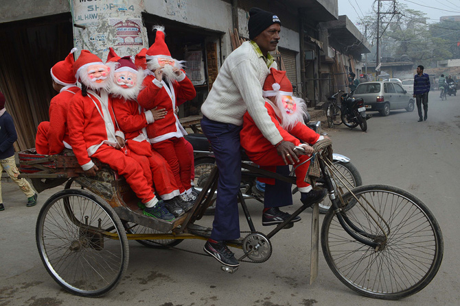 Indian schoolchildren dressed as Santa Claus ride on a cycle-rickshaw through a street in Amritsar on December 24,2012, ahead of Christmas Day. Despite Christians forming a little over 2 percent of the billion plus population in India, with Hindus comprising the majority, Christmas is celebrated with much fanfare and zeal throughout the country. ? Photo by AFP