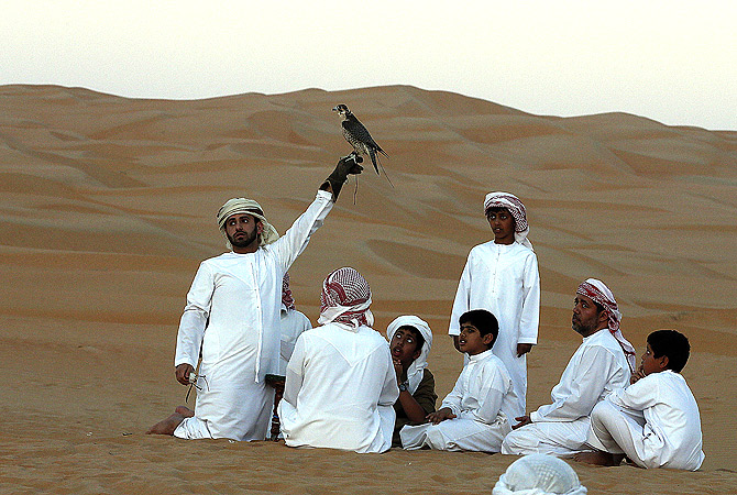 An Emirati man holds a falcon as children watch at the Liwa Desert. ? AFP Photo