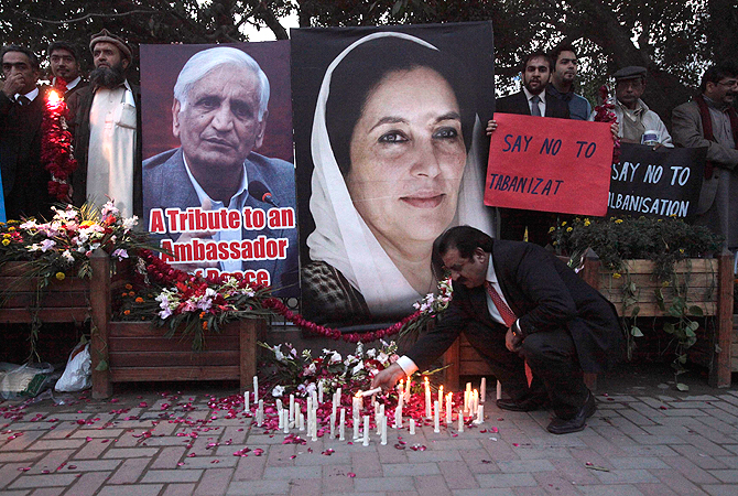 A man lights a candle near posters of former Prime Minister of Pakistan Benazir Bhutto (R), and the provincial minister for local government Bashir Ahmad Bilour, who was assassinated in a bomb attack on Saturday, during a vigil marking Bhutto's 6th death anniversary in Lahore December 26, 2012. ? Reuters Photo