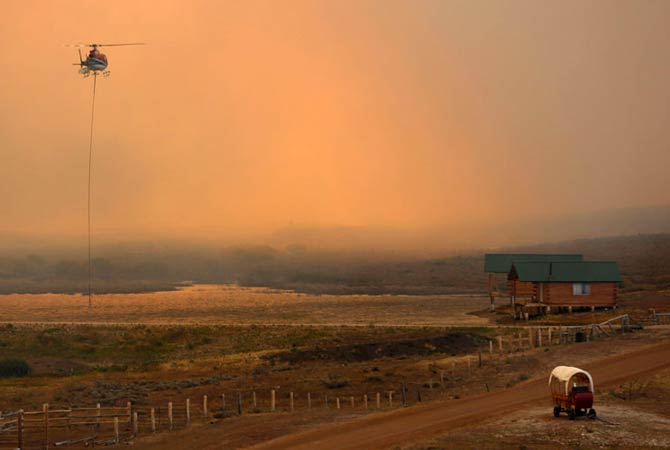 A firefighting helicopter fills a bucket of water in heavy smoke as the North Merna wildfire burns in the Bridger National Forest west of the town of Pinedale in Sublette County, Wyoming September 16, 2012.