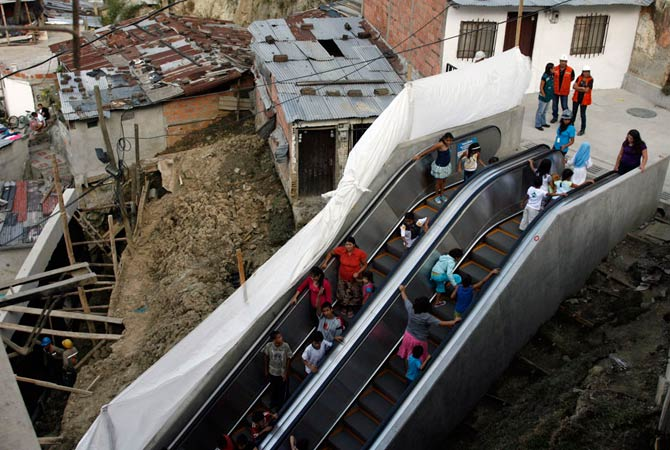 People travel on an outdoor public escalator at Commune 13 in Medellin January 12, 2012. A huge 384 meters (1,260 ft) long outdoor escalator, divided into six sections, has been erected in one of the poorest districts of Colombia's second largest city to help the 12,000 residents there get around.