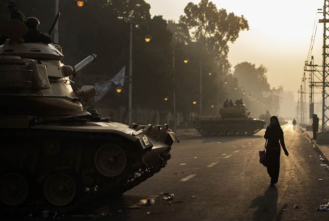 Egyptians walk past a line of army tanks stationed outside the presidential palace in Cairo.