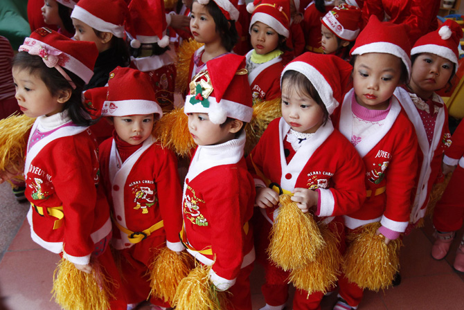 Children dressed in Santa Claus outfits line up before a Christmas celebration at a kindergarten in Hanoi December 24, 2012. ? Photo by Reuters