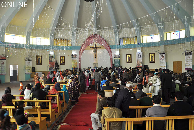 Members of Christian community performing religious rituals as they celebrate Christmas at a local church in Faisalabad. ? Online