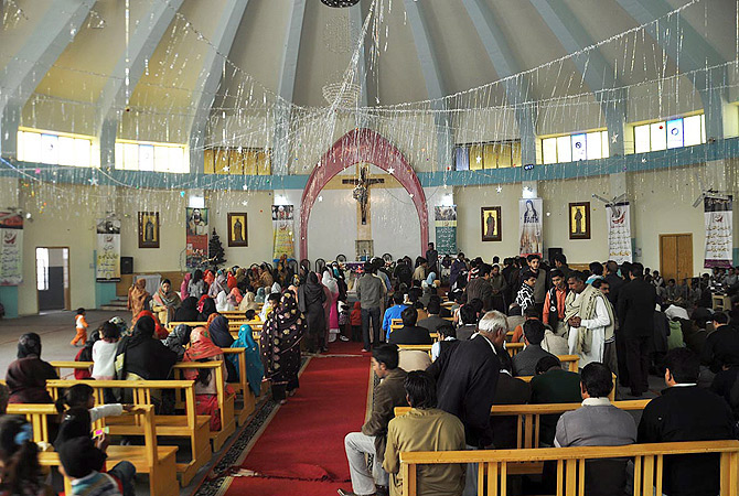 Members of Christian community performing religious rituals as they celebrate Christmas at a local church in Faisalabad. ? Online Photo