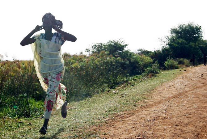 A woman runs along a road during an air strike by the Sudanese air force in Rubkona near Bentiu April 23, 2012.