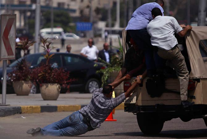 "Members of ""Field Marshal Hussein Tantawi,"" a group consisting of official and police guards, try to ride a military police vehicle after a funeral for soldiers who were killed during an attack at a checkpoint along the Sinai border with Israel by unknown gunmen, at the tomb of the late President Anwar al-Sadat and the Unknown Soldier monument in Cairo August 7, 2012"